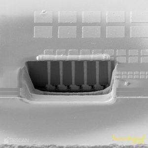 Velká plocha průřezu 3D IC ukazující 5 Cu TSV v křemíku spolu s pájecími kuličkami ve spodní části. Průřez byl připraven za méně než jednu hodinu pomocí Xe Plasma FIBu.