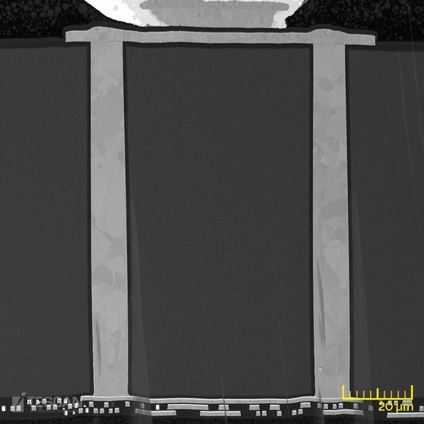 BSE cross-sectional view of 2.5D stacked-die showing two Cu TSVs passing through silicon interposer in order to connect upper metal layers to additional backside metal layers